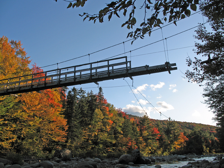 A photo capturing the progress of disassembly of a suspension bridge from the Pemigewasset Wilderness in the White Mountains of NH.